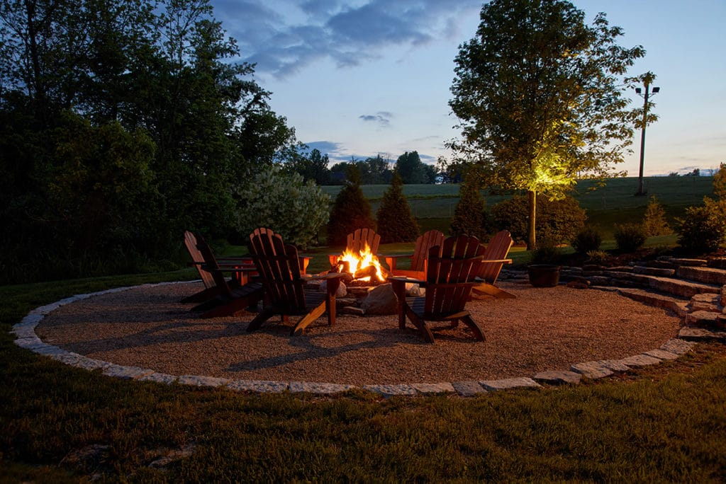 Willis Graves fire pit ring with wood adirondack chairs at night